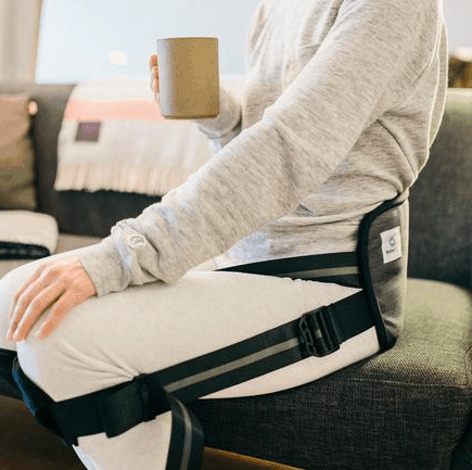 BetterBack worn by person sitting on sofa holding a mug