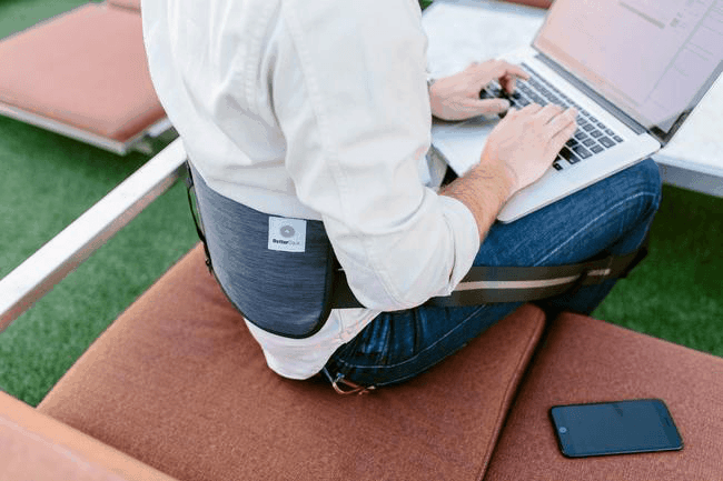 BetterBack worn by person sitting on couch with laptop