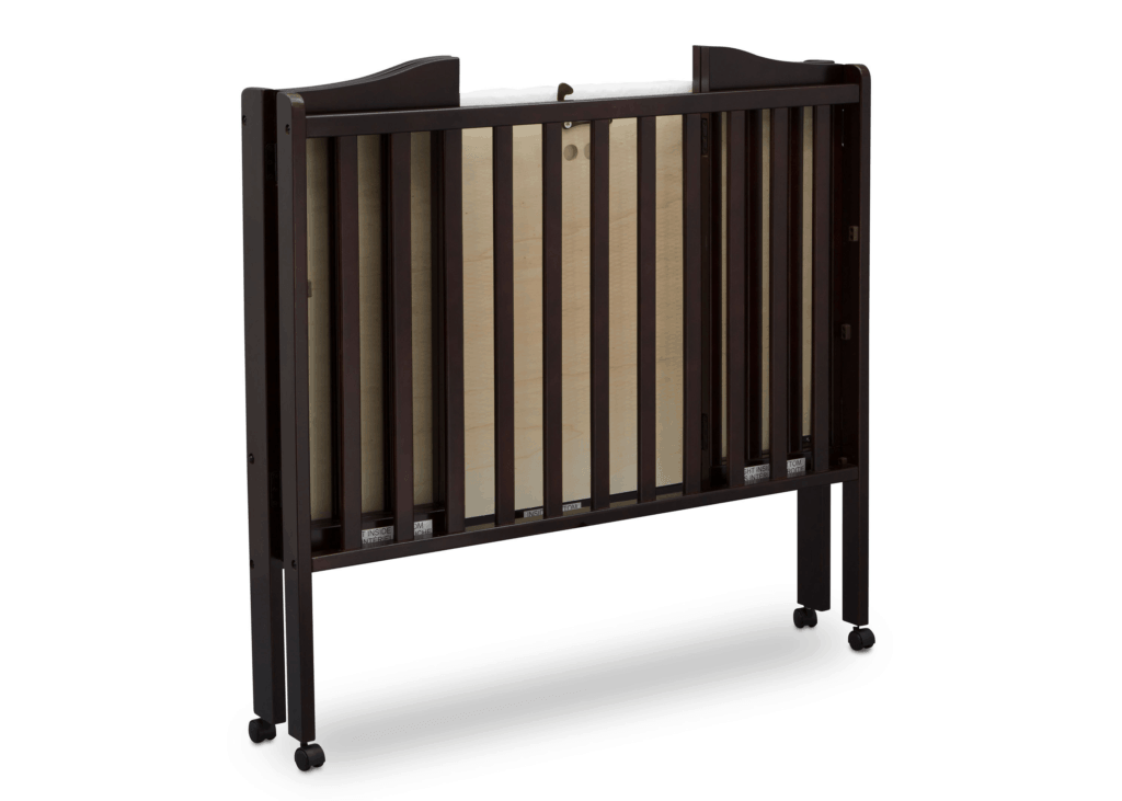 Delta Children Portable Mini Crib in brown folded on wheels angled front view