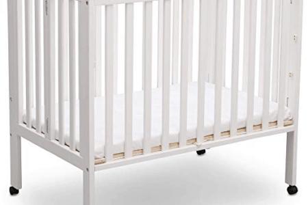 Delta Children Portable Mini Crib in white open on wheels