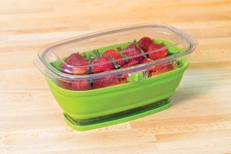 Progressive Prepworks produce keeper in green open on table filled with strawberries
