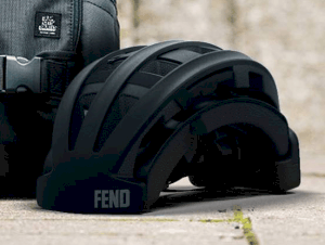 Fend helmet in black folded shown outside next to a backpack