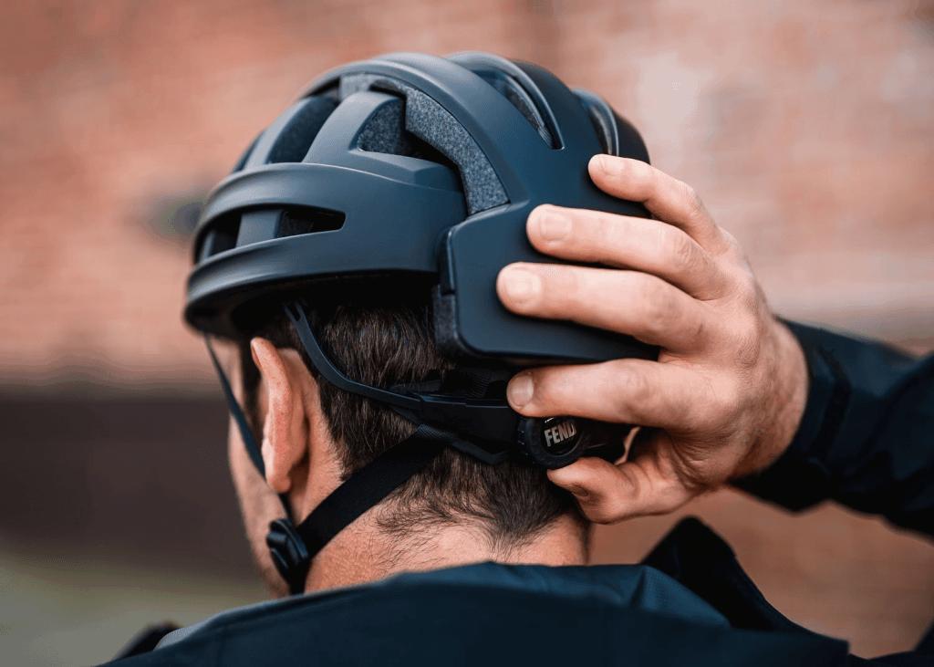 Fend helmet rear view showing man adjusting tightness adjustor