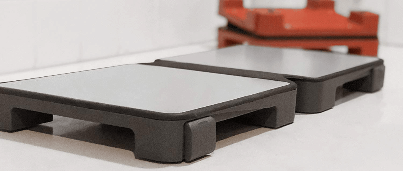 HotMat Hot Plate in grey open on counter in foreground with red folded in background