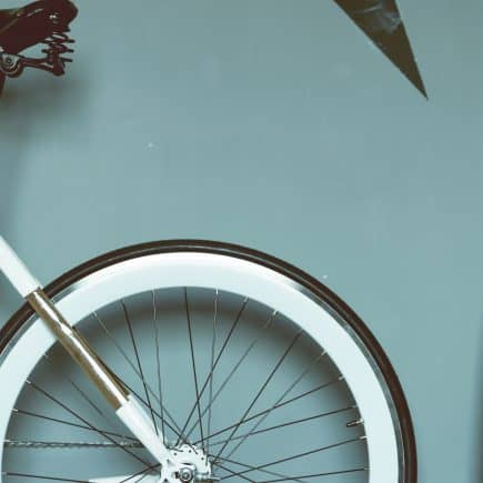 Rear of bicycle inside room with plant by michal wichrzynski from unsplash