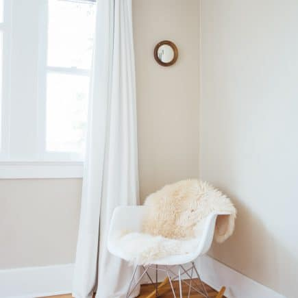 white nursery with daylight in window and white rocking chair