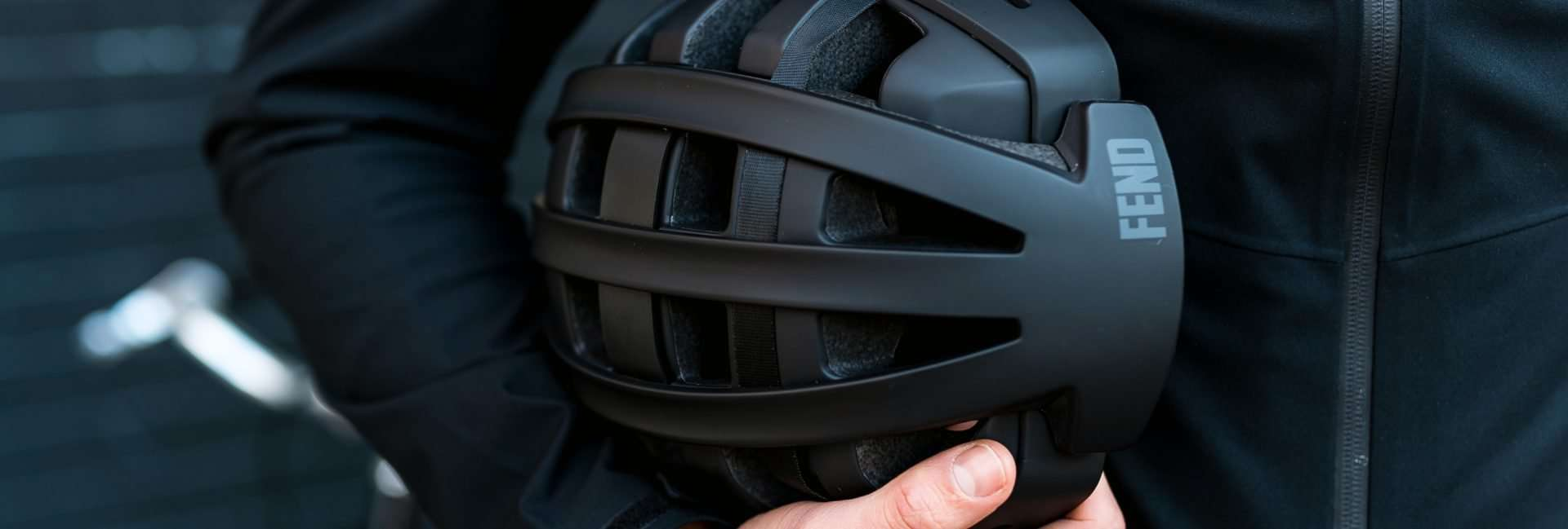 Fend helmet in black tucked under arm