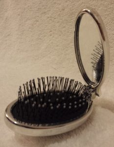 Wet Brush in silver half folded showing mirror on handle